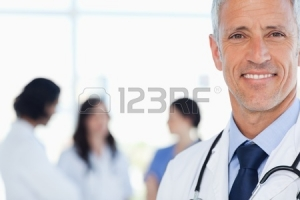 16184788-doctor-showing-a-beaming-smile-with-his-medical-interns-behind-him